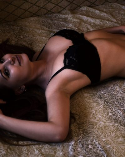 Portrait of an attractive and pretty young and sexy caucasian girl in elegant black underwear lies on the bed in the beige hotel room
